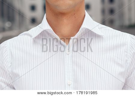 Closeup on male elegant shirt with collar. Businessman wearing white shirt on the background of office building business center.