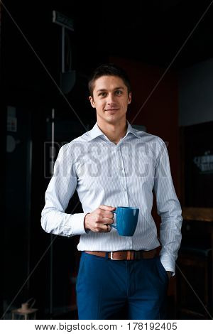Charming young male with cup of coffee. Smiling relaxed businessman standing in cafe. Coffee break.