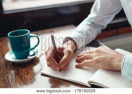 Close up of hands of a businessman writing in a notebook and a cup of coffee. A freelance man is working in a cafe. Coffee break.