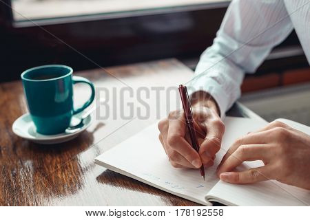 Concept To do list message on notebook with businessman hands, pen and coffee cup on wooden table.