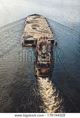 Tugboat pushing barge with sand. Nautical transportation