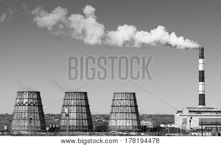 Thermal power station with smoking chimneys. View from afar. Horizontal black and white photo.