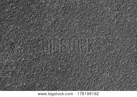 Texture of rough plaster. Horizontal background with a stucco exterior wall. Dark gray.