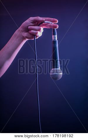 Hand With Microphone On A Black Background, The Music Concept, Beautiful Lighting On The Stage