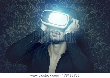 Young caucasian man in virtual reality headset enjoying simulation in cinematic style and light