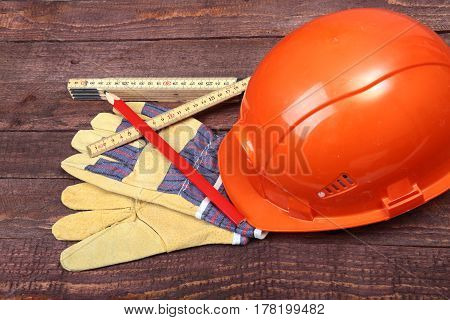 Orange hard hat, safety glasses, gloves and measuring tape on wooden background. you can place your text.