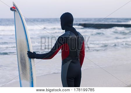 Surfer with surfboard standing. He wears a wetsuit