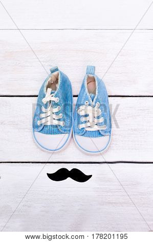 Mustache and blue children's shoes stand on a white wooden background. Vertical photography. flat lay