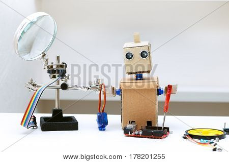 Robot with his hands holding a screwdriver and next to lie other parts for assembling the robot