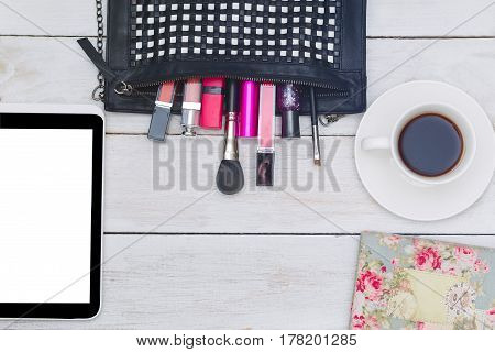 Top view of female fashion accessories - handbag cosmetics and electronic devices.