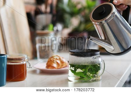 Home. Woman making tea in kitchen