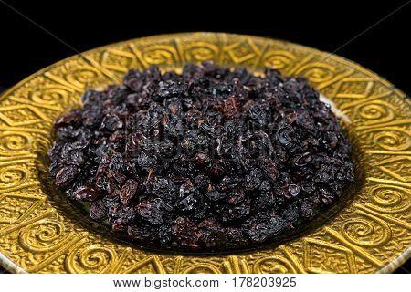 Black raisins in golden plate on black background