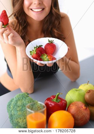 Girl sitting in the kitchen on the desk with fruit .