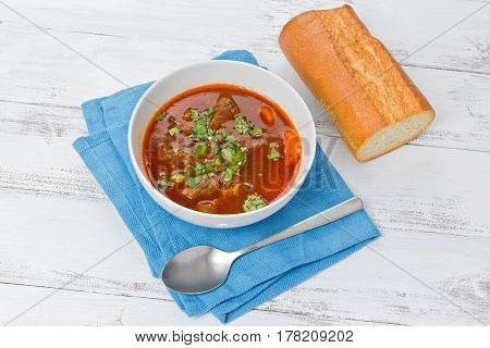 Lemongrass beef stew in a white bowl with a piece of baguette on a white background.