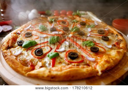 Delicious hot and fresh pizza with steam and smoke