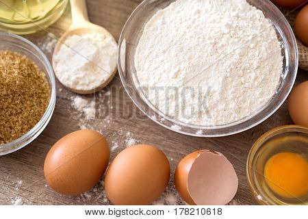 eggs and flour basic ingredients for baking on wooden table