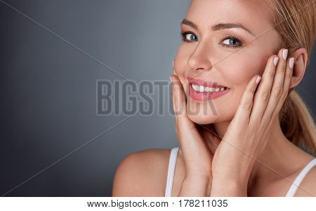 Smiling woman enjoying in her healthy skin, middle aged lady touching her face