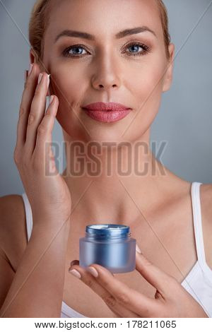 Middle aged woman uses the cream to rejuvenate skin cells
