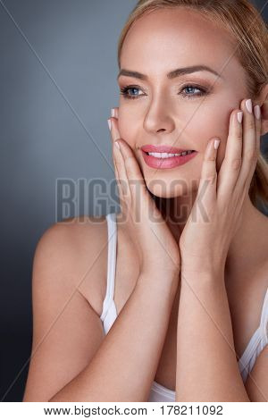 Beautiful spa woman touching her face, perfect fresh skin,  pure beauty middle aged model, skin care concept