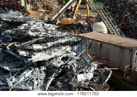 scrap metal yard with compressed car bodies in the foreground