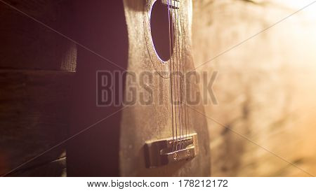 Acoustic guitar leaning on grungy wooden wall.