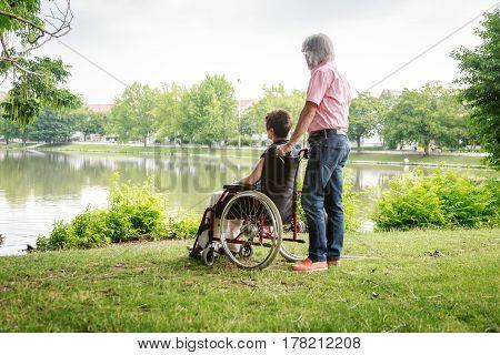 Senior couple in wheelchair, enjoying time outdoors.