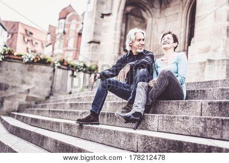 Senior couple taking a rest next to church, Tuebingen, Germany