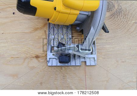 Yellow Circular Power Saw Cutting Wood Close-up