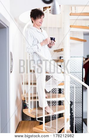 senior woman wearing pajamas is coming down the stairs in her apartment