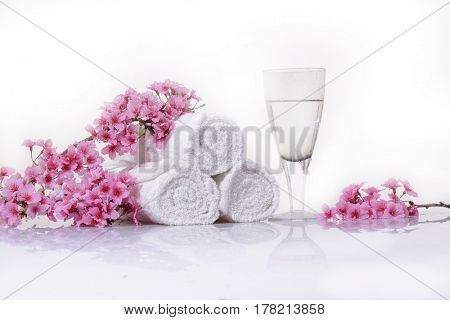 Branch pink cherry on three rolled towel ,glass cup isolated