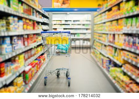 shopping cart standing in a supermarket's aisle
