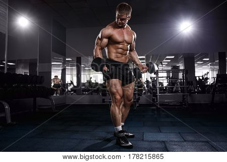 Athlete Muscular Bodybuilder Man Posing With Dumbbells In Gym.