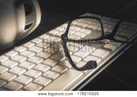Vintage monochrome image of the keypad of the computer and glasses. Semi-antique stylization. Scratches. Low contrast. Monophonic toning. Blackout at the edges.Horizontal format. Indoors. Photo.