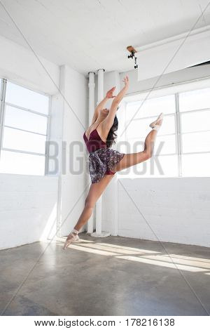 Beautiful young flexible ballerina is dancing in studio