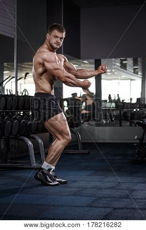 Athlete Muscular Bodybuilder Man Demonstrates His Muscles In Gym.