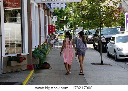 HARBOR SPRINGS, MICHIGAN / UNITED STATES - AUGUST 4, 2016: Pedestrians walk past boutiques along West Main Street in downtown Harbor Springs.