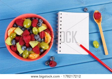 Fresh Fruit Salad And Notepad For Writing Notes, Healthy Lifestyle And Nutrition Concept