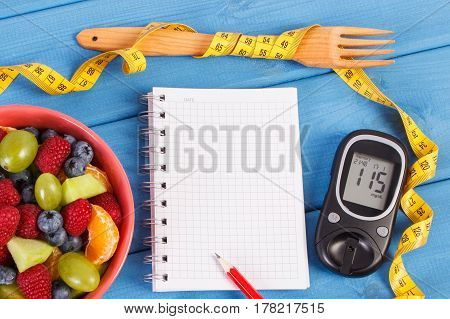 Fresh fruit salad glucometer with result of sugar level tape measure and notepad for writing notes or resolutions concept of diabetes diet slimming healthy lifestyles and nutrition