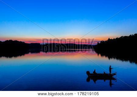 A sunset image of people fishing in silhouette on Marsh Creek Lake in Chester County, PA.