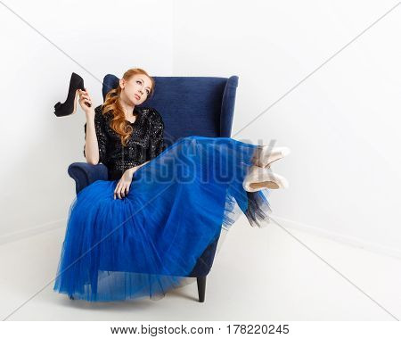 Pretty ballerina in tutu and pointe shoes sits in a chair. She holds high-heeled shoes.