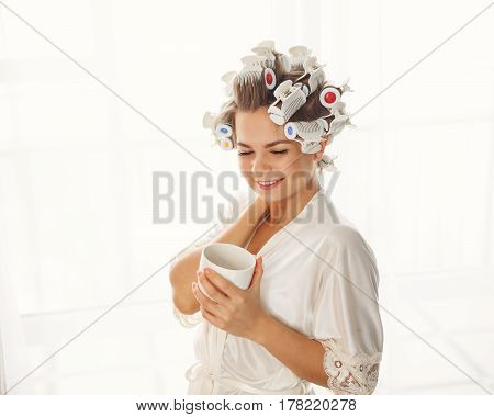 Young attractive housewife against the window. Girl in a bathrobe and curlers drinking morning coffee. Good morning. She holds a mug of hot drink
