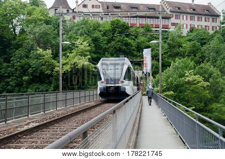 NEUHAUSEN AM RHEINFALL SWITZERLAND - JUNE 10 2013: Modern train on bridge at Rheinfall largest plain waterfall in Europe