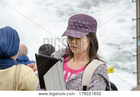 Young Asian Girl Do Selfie By Tablet At Rhine Falls, The Largest Plain Waterfall In Europe