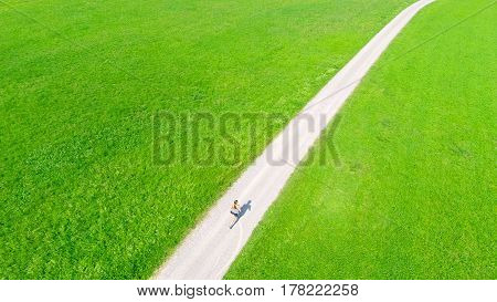 aerial view of young woman jogging in the fields