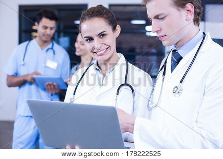 Doctors using laptop and smiling at camera while her colleagues discussing behind