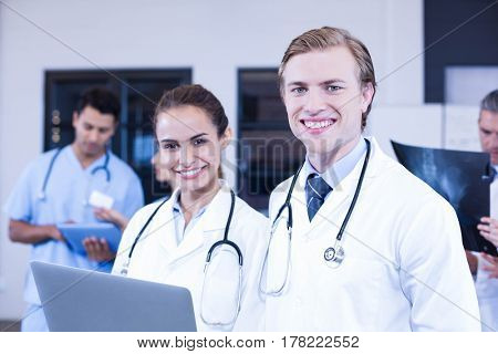 Portrait of doctors using laptop and smiling while her colleagues discussing behind