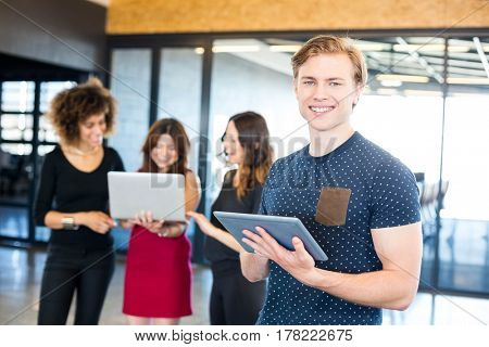 Portrait of man smiling and holding digital tablet while his colleagues standing behind him in office