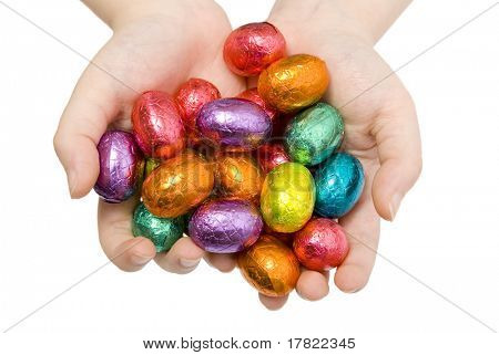 A child holding out a handful of colourful Easter Eggs
