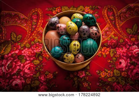 Easter. Colorful Eggs In A Wooden Bowl  On A Background Of Patte