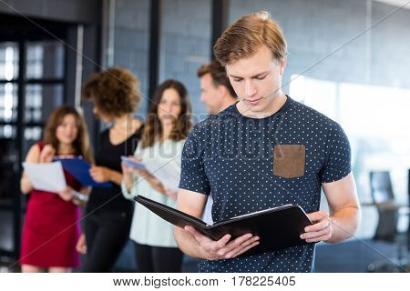Man reading a document while her colleagues standing behind in office